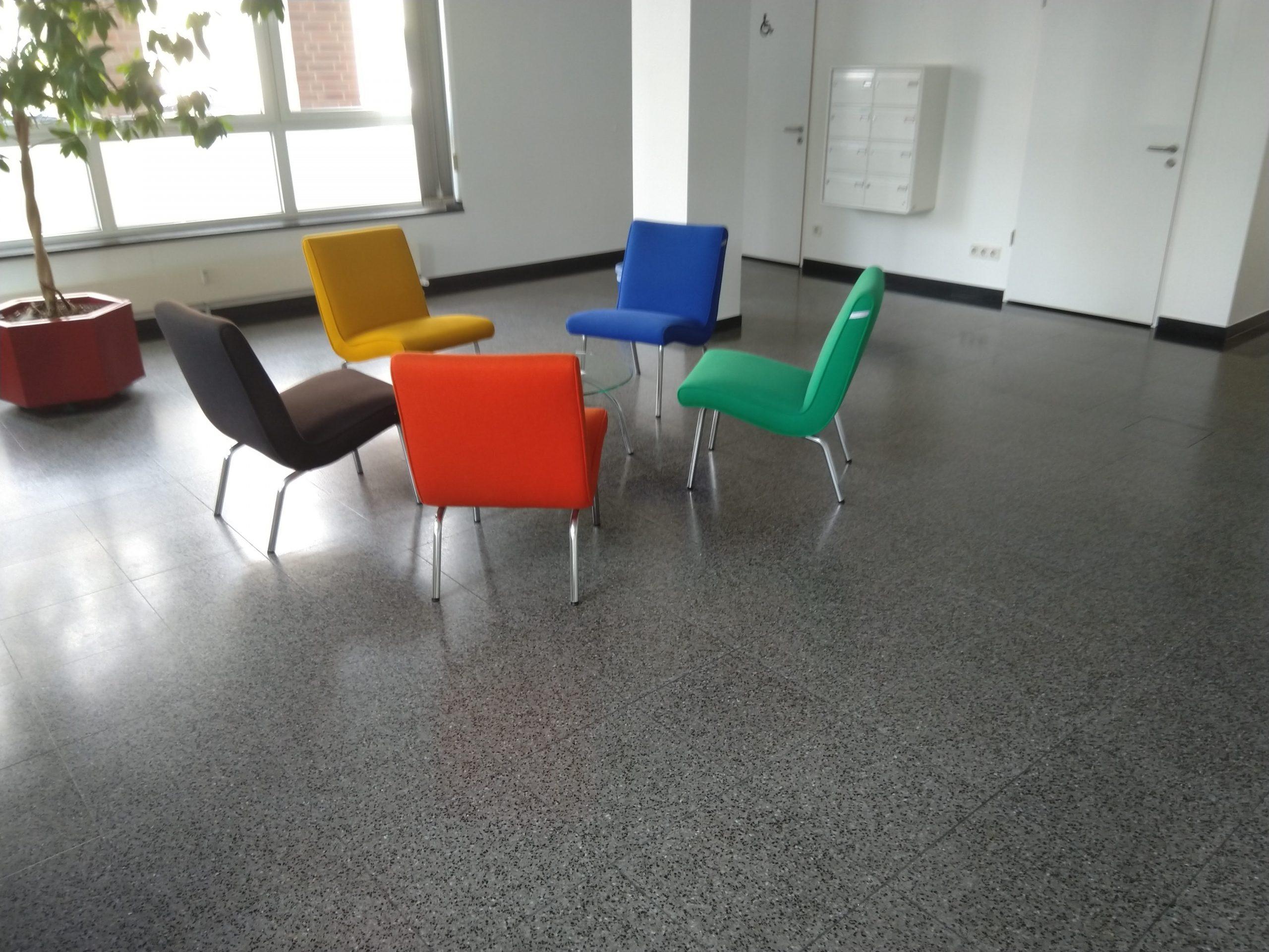 gelber, roter, grüner, roter und schwarzer Stuhl steht im Empfangsbereich - Wischen ist Macht JAMES CLEAN GMBH Ihr Servicepartner seit 1996 aus Mönchengladbach aus Mönchengladbach